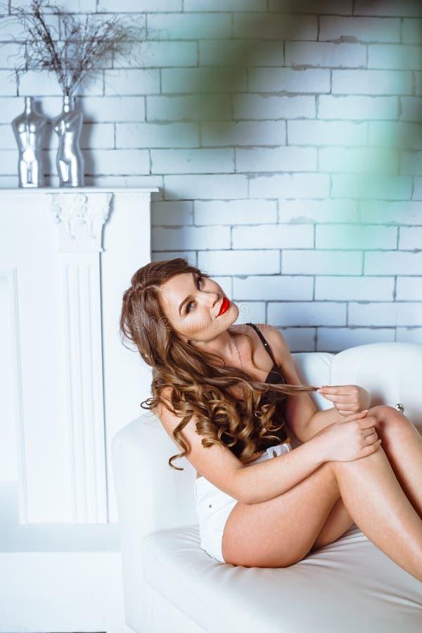 Flicka i bodysuit på soffan royaltyfria foton