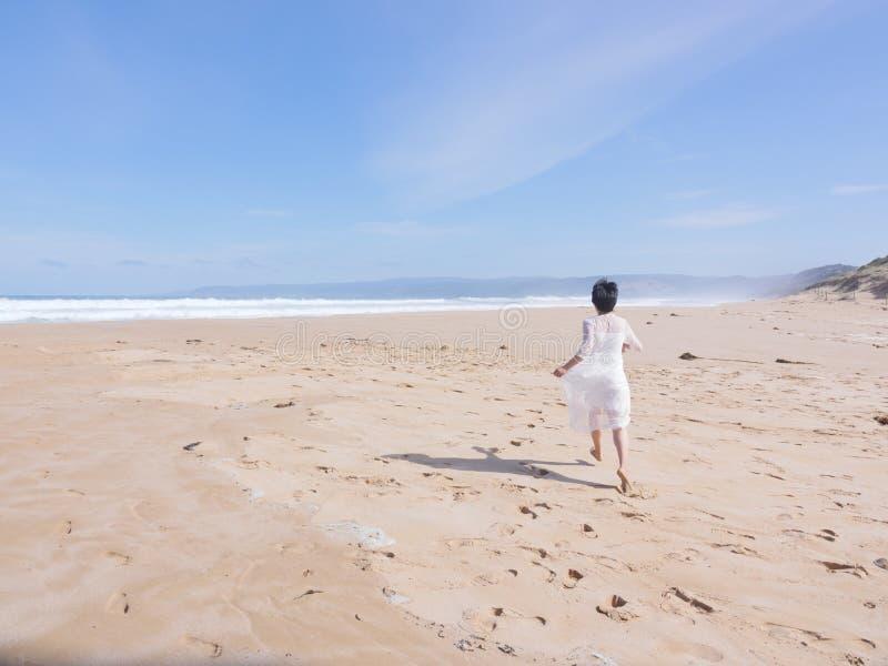 Flicka i bröllopsklänningspring längs stranden royaltyfri foto
