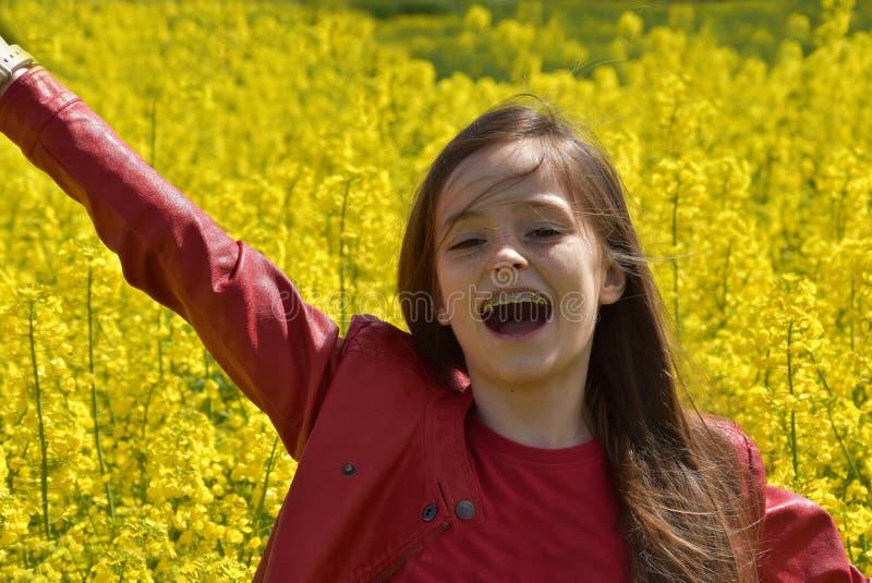 Flicka i canolafält arkivbilder