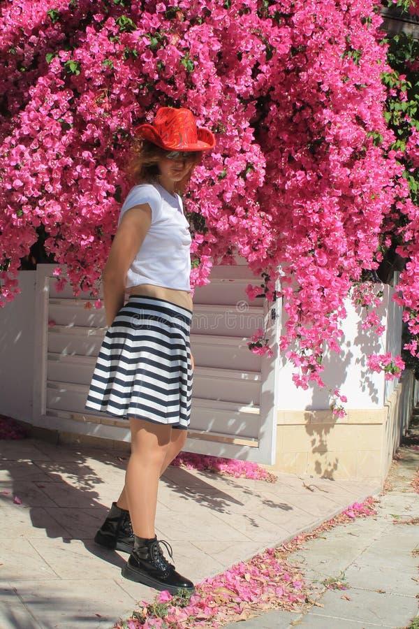 Flicka i cowboys hatt bredvid rosa blommor royaltyfri fotografi