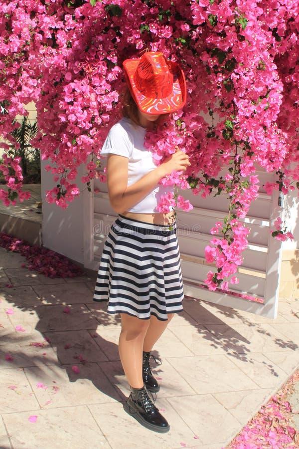 Flicka i cowboys hatt bredvid rosa blommor royaltyfri foto