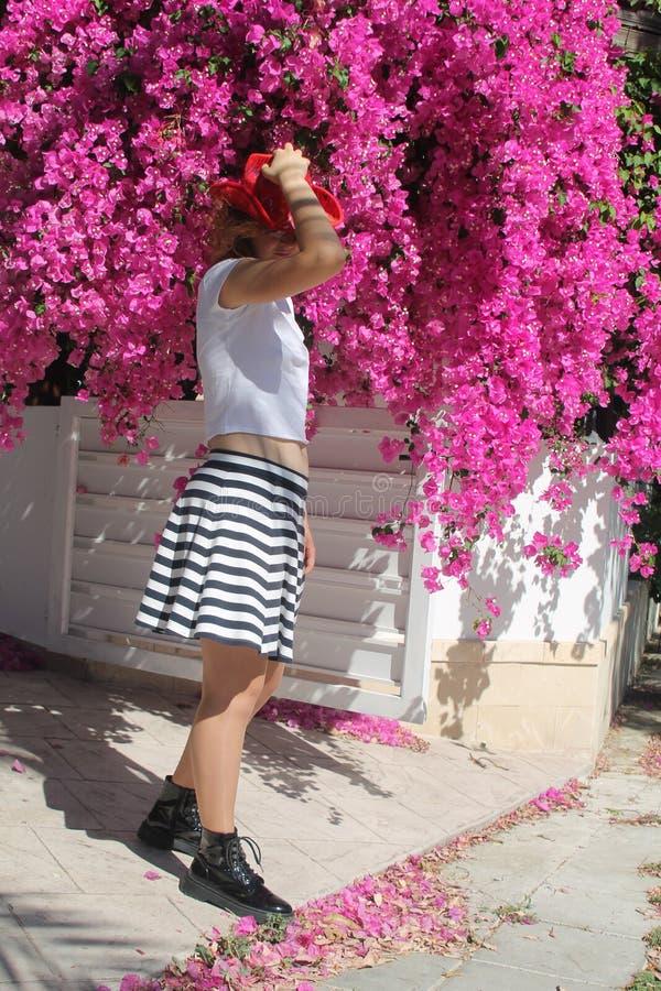 Flicka i cowboys hatt bredvid rosa blommor arkivfoto