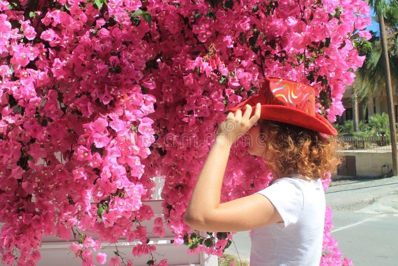 Flicka i cowboys hatt framme av rosa blommor arkivfoto