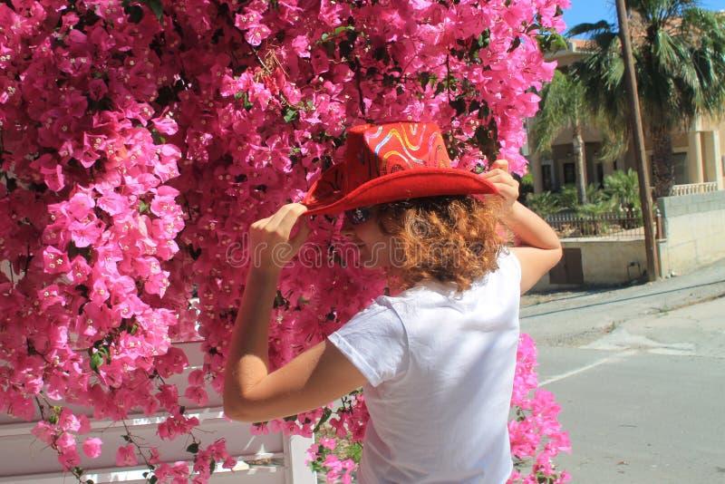 Flicka i cowboys hatt framme av rosa blommor arkivbild