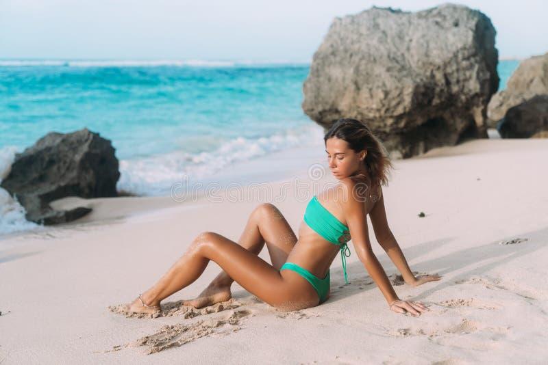 flicka i den blåa baddräkten som poserar på solig dag på den sandiga stranden royaltyfria foton