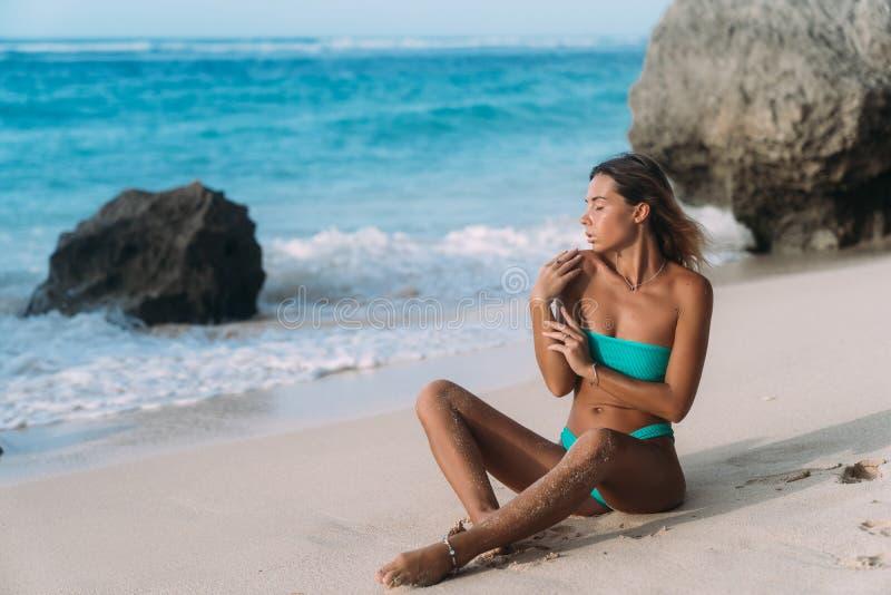 flicka i den blåa baddräkten som poserar på solig dag på den sandiga stranden arkivbilder