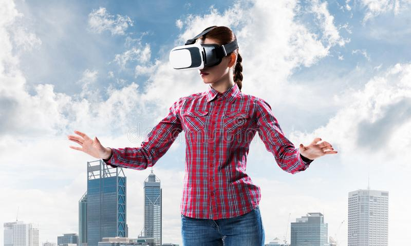 Flicka i den kontrollerade skjortan som bär VR-exponeringsglas som erfar en annan verklighet royaltyfri foto