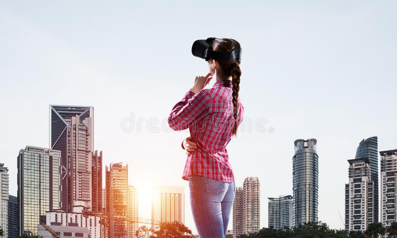 Flicka i den kontrollerade skjortan som bär VR-exponeringsglas som erfar en annan verklighet royaltyfri fotografi
