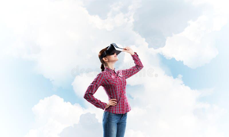 Flicka i den kontrollerade skjortan som bär VR-exponeringsglas som erfar en annan verklighet arkivfoton