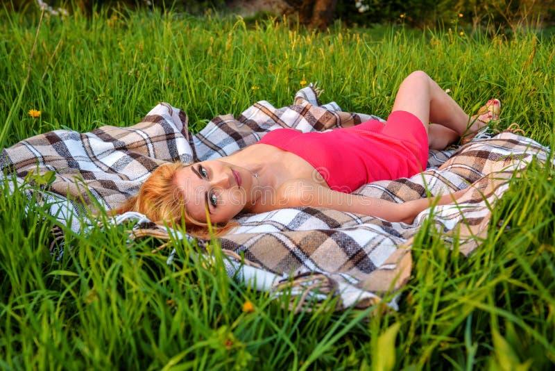 Flicka i den röda klänningen som ligger på gräset arkivbilder