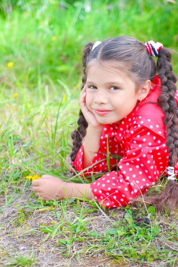 Flicka i den röda vindtygsjackan som ligger på gräset royaltyfria bilder