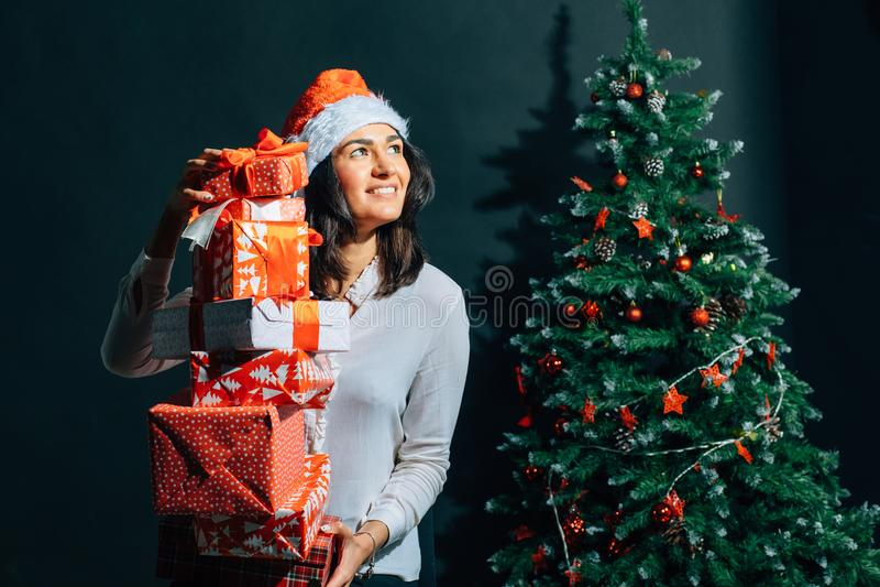 Flicka i den santa hatten nära ett julträd med gåvor arkivfoton