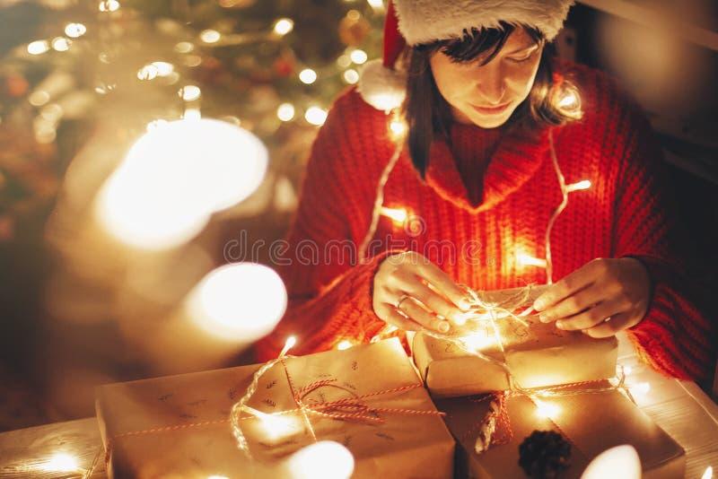 Flicka i den santa hatten och den röda tröjan som in slår in julgåvor royaltyfria bilder