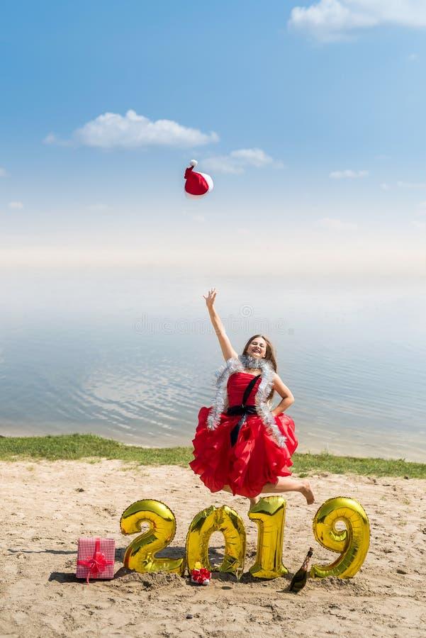 Flicka i den santa hatten som hoppar på stranden royaltyfri fotografi