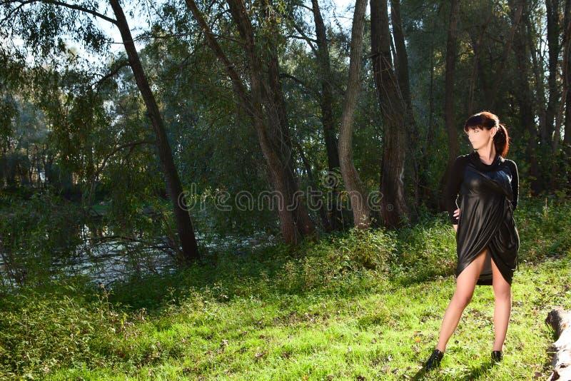 Flicka i den svarta klänningen som poserar på gläntan av skogen royaltyfria bilder