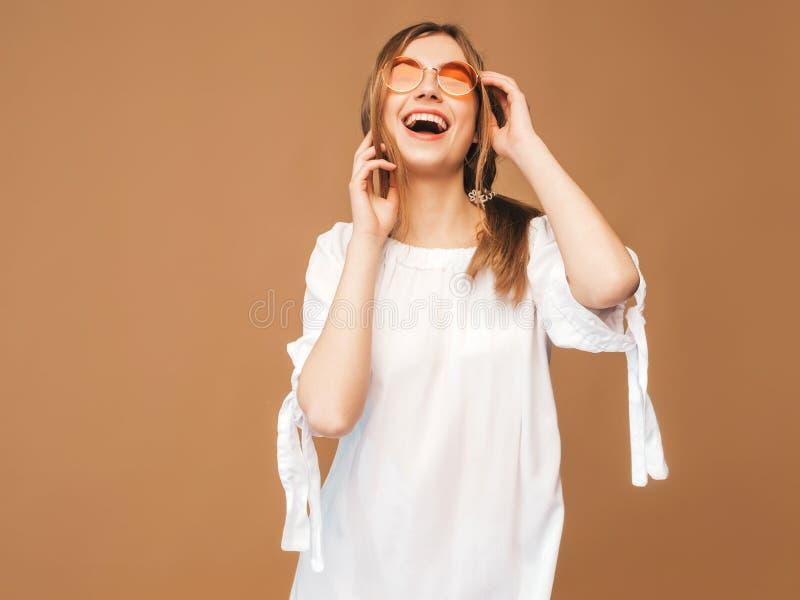 Flicka i den vita hipsterkl?nningen f?r sommar Modellera att posera p? guld- bakgrund i solglas?gon royaltyfri bild