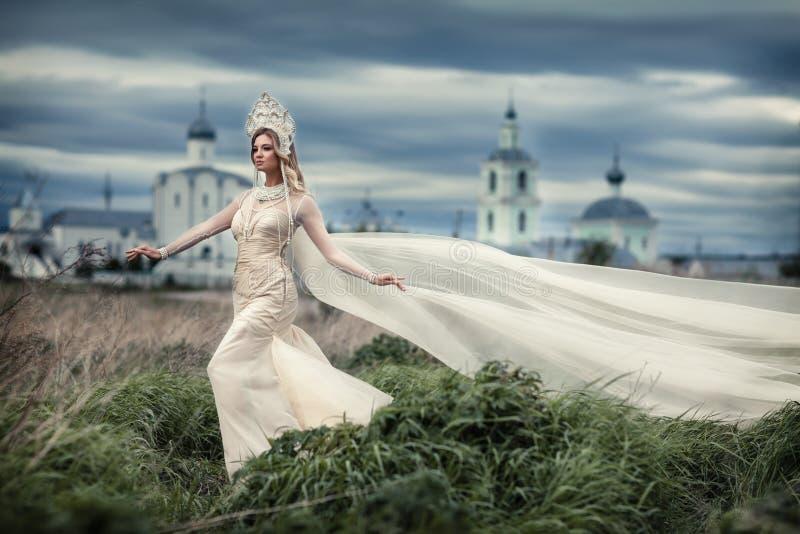 Flicka i den vita klänningen på bakgrund av kyrkan royaltyfria bilder
