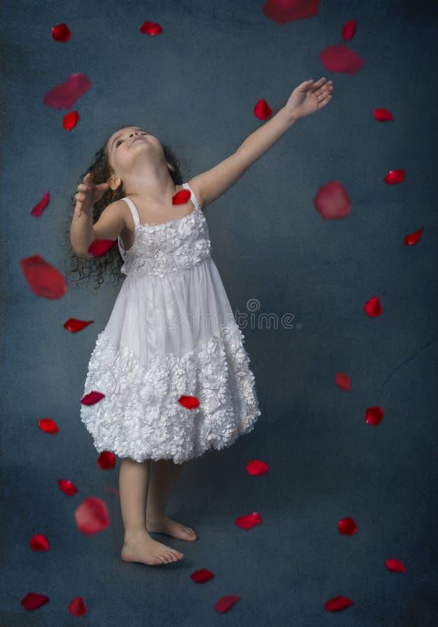 Flicka i den vita klänningen som ser upp på fallande blommakronblad royaltyfria foton