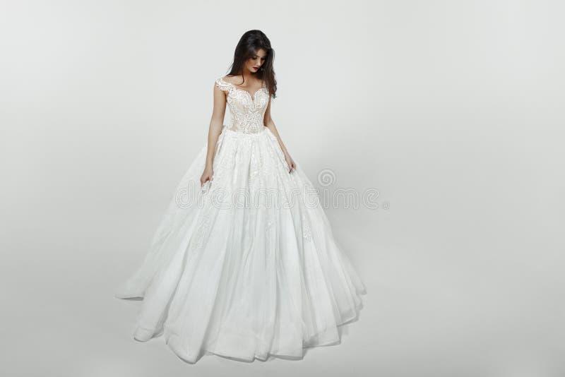 Flicka i den vita prinsessamodebröllopsklänningen som isoleras på en vit bakgrund arkivbild