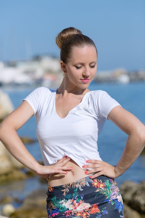 Flicka i den vita T-tröja och kjolen på den steniga kusten royaltyfri foto