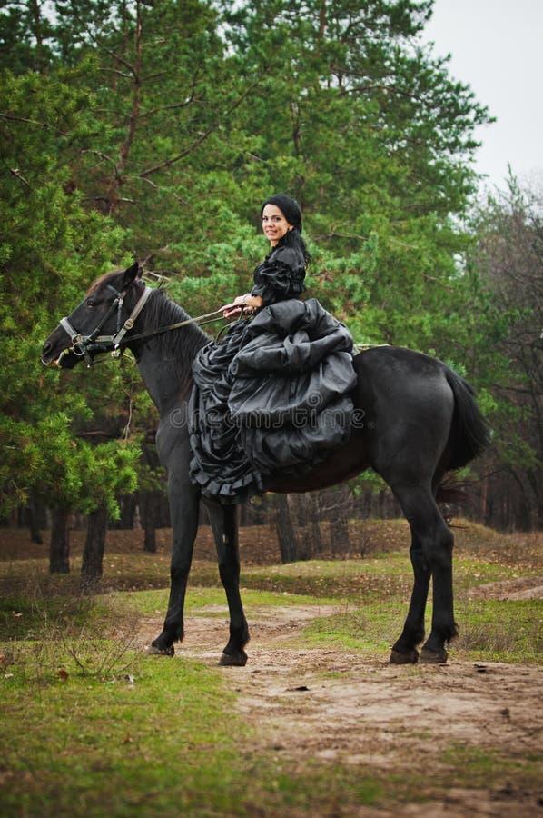 Flicka i dräkt på hästrygg royaltyfri foto
