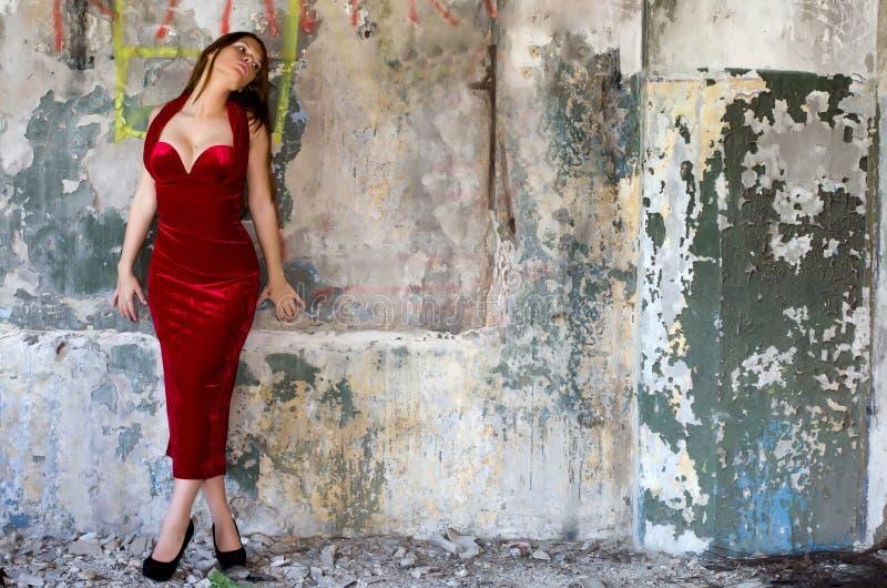 Flicka i en aftonklänning mot en gammal vägg royaltyfria foton