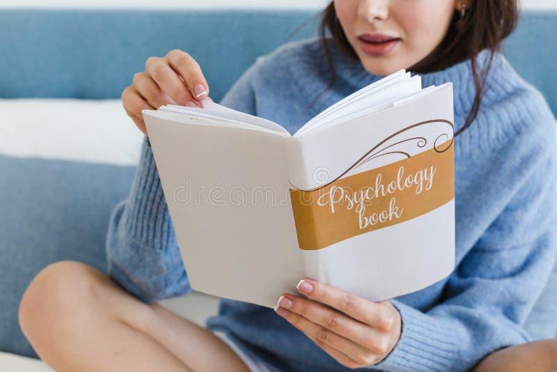 Flicka i en blå tröja som läser en bok på psykologi som sitter på sängen i en hemtrevlig inre royaltyfri bild