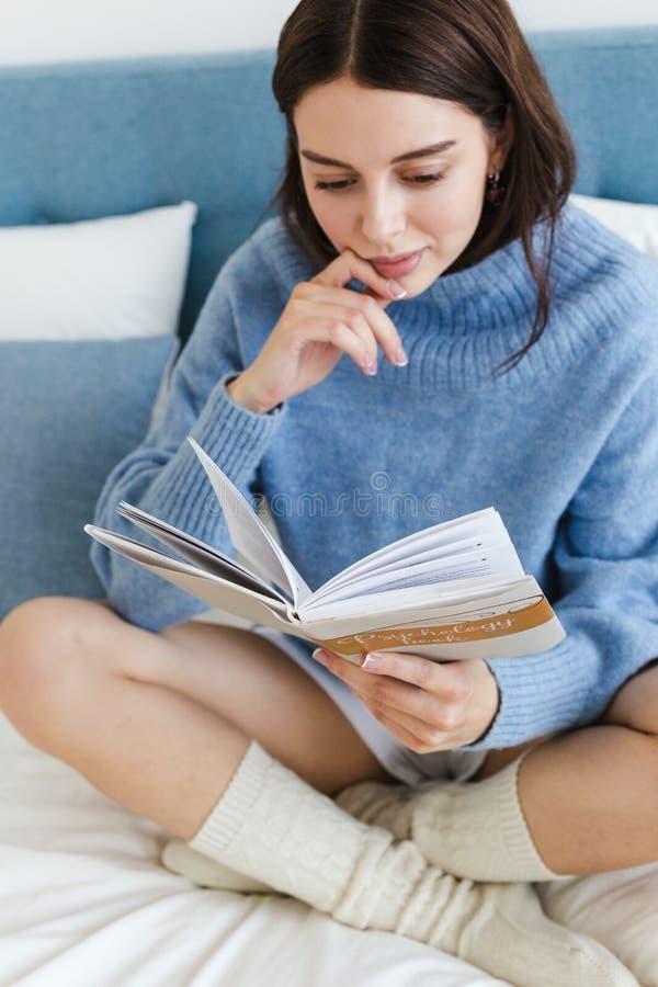 Flicka i en blå tröja som läser en bok på psykologi som sitter på sängen i en hemtrevlig inre arkivfoton