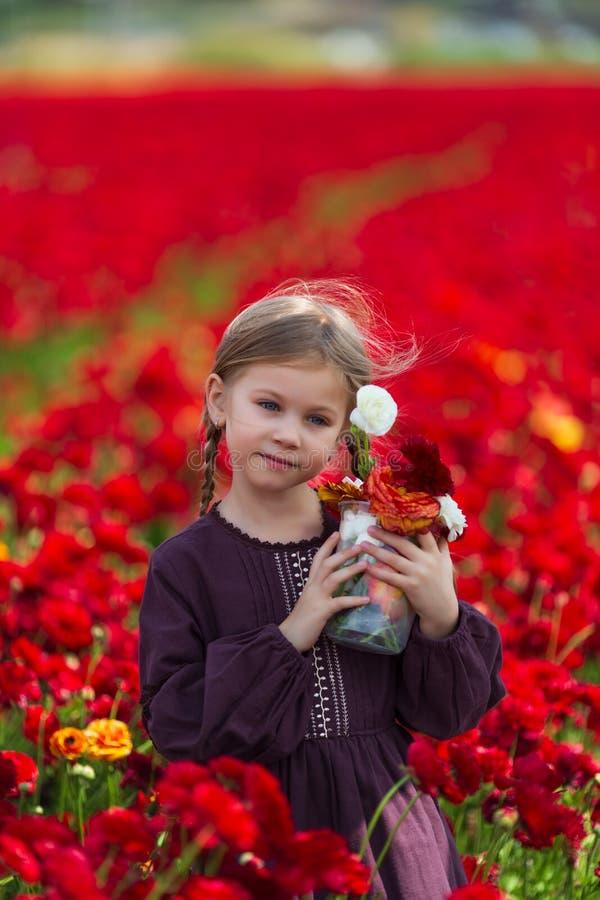 Flicka i en burgundy sommarklänning som väljer blommor i ängen fotografering för bildbyråer