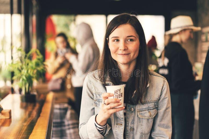 Flicka i en coffee shop med en kopp kaffe arkivfoton