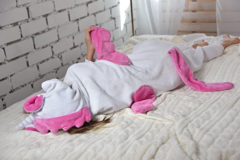 Flicka i en enhörningdräkt som ligger på sängen, läge i vit royaltyfria foton
