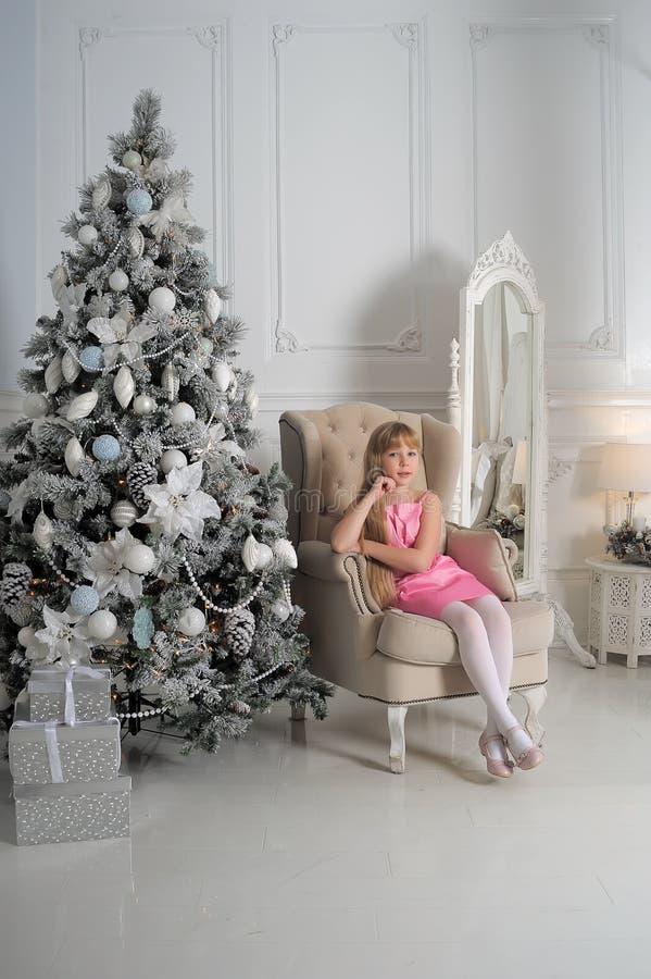 Flicka i en gräns - rosa färger klär sammanträde i en stol på julgranen royaltyfria bilder