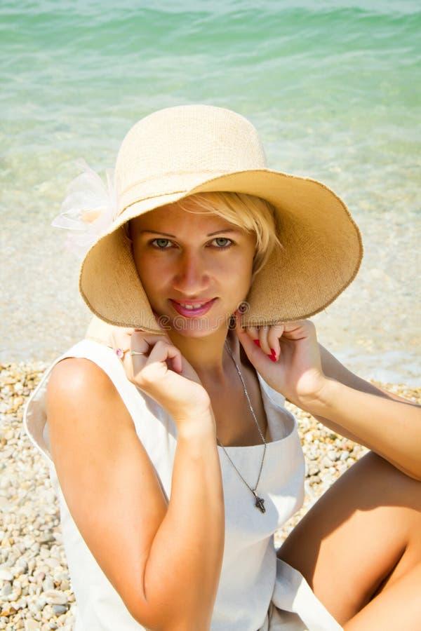 Flicka i en hatt på stranden. arkivfoto
