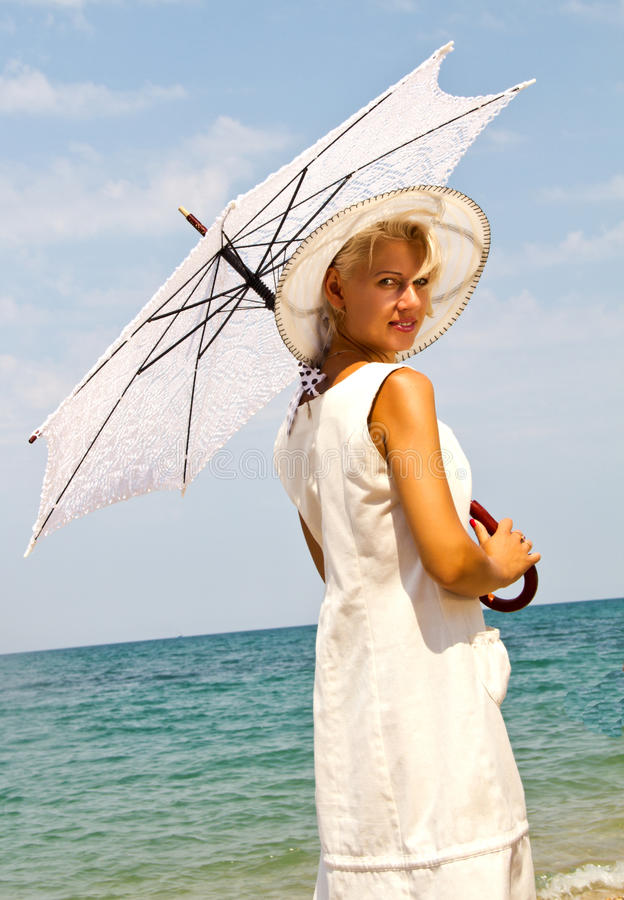 Flicka i en hatt på stranden. arkivbild