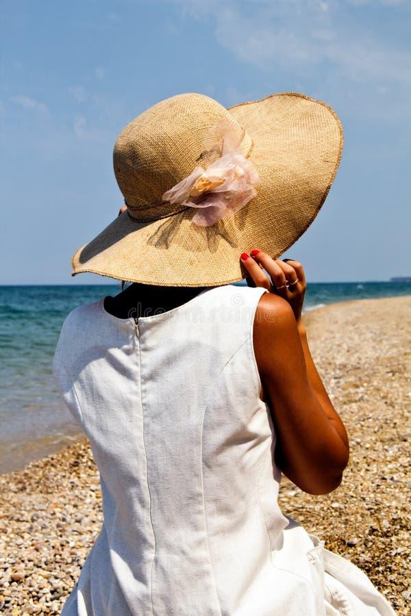 Flicka i en hatt på stranden. arkivbilder