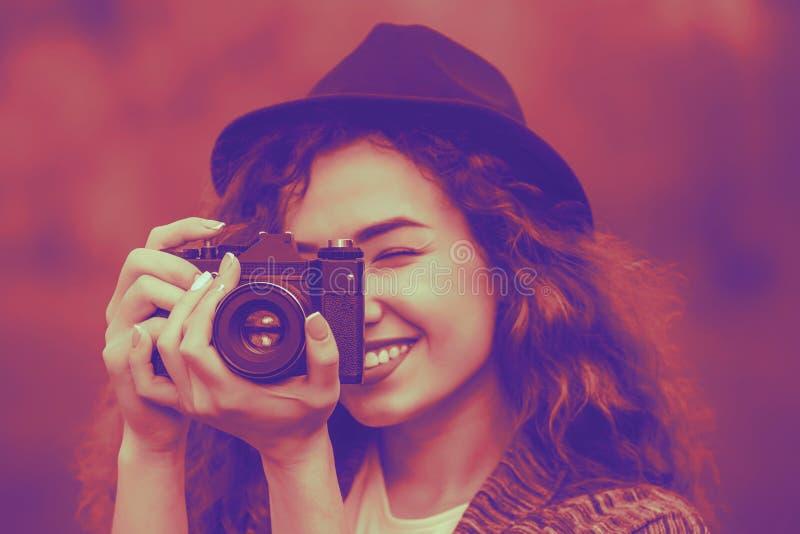 Flicka i en hatt som ler och fotograferar naturen royaltyfria bilder