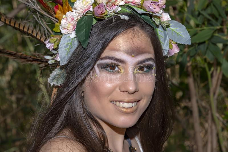 Flicka i en indianhuvudbonad mot bakgrunden av gr?n l?vverk royaltyfri bild