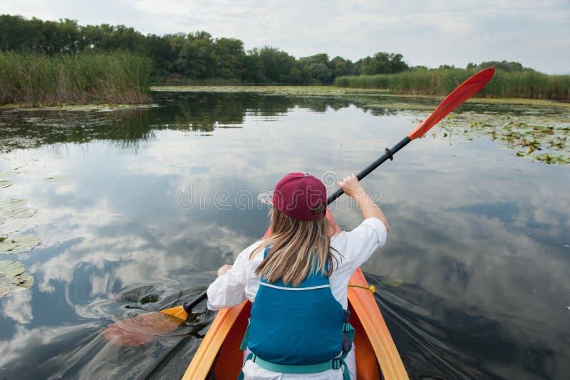 Flicka i en kajak på en flod royaltyfria bilder