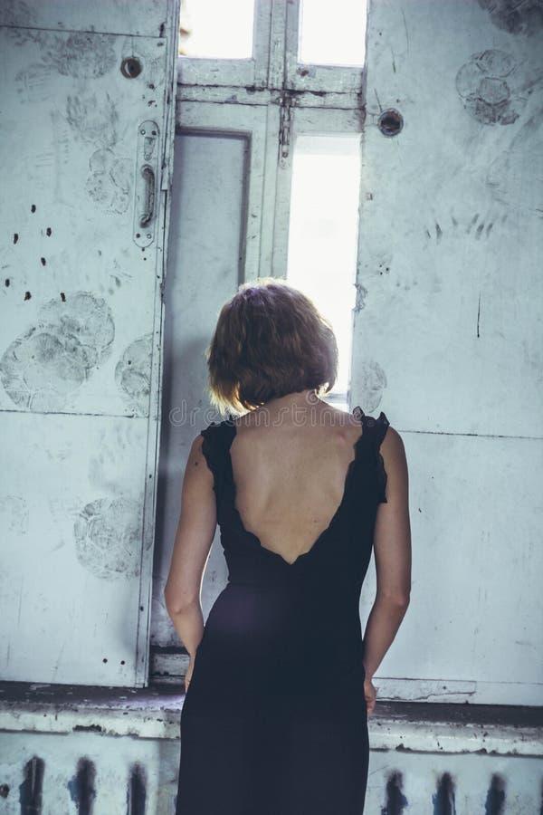 Flicka i en klänning i ett gammalt hus royaltyfri fotografi