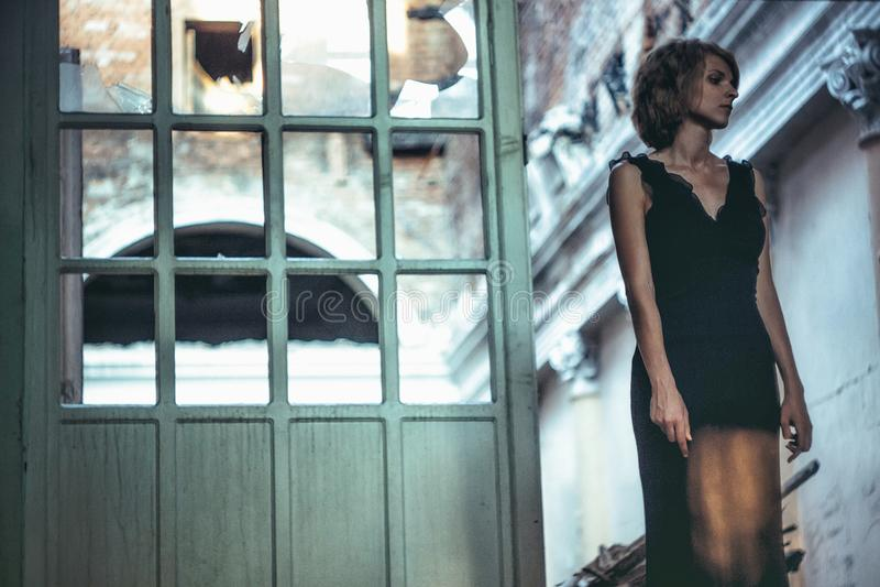 Flicka i en klänning i ett gammalt hus royaltyfri bild