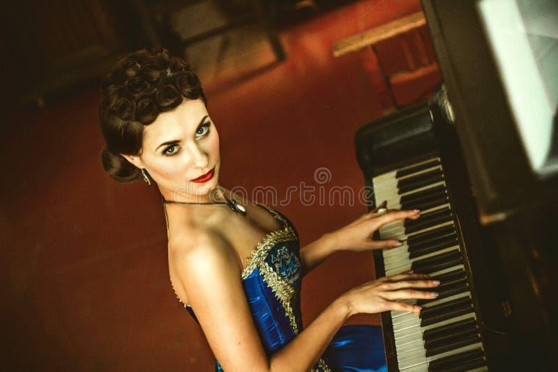 Flicka i en klänning på pianot arkivfoto
