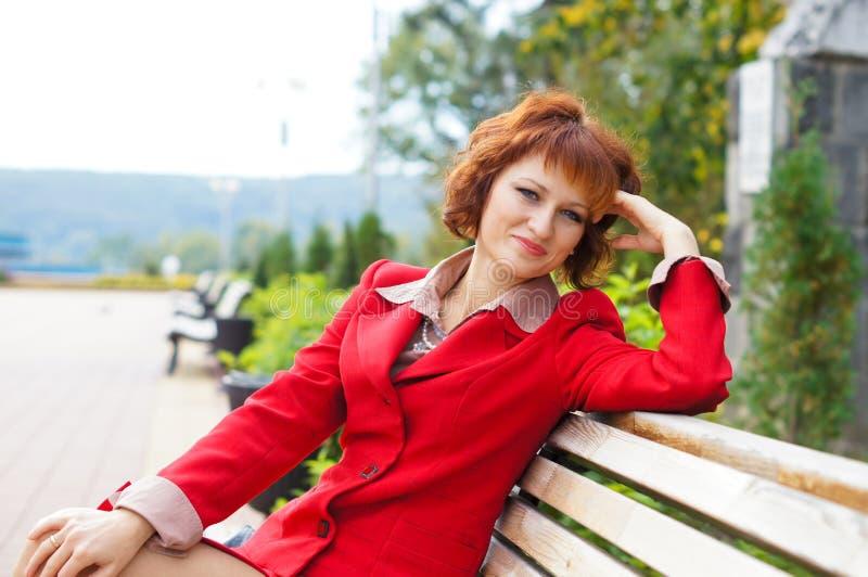 Flicka i en röd affärsdräkt arkivfoto