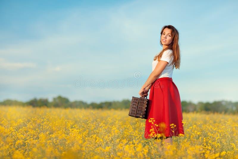 Flicka i en röd kjol med resväskan royaltyfria bilder