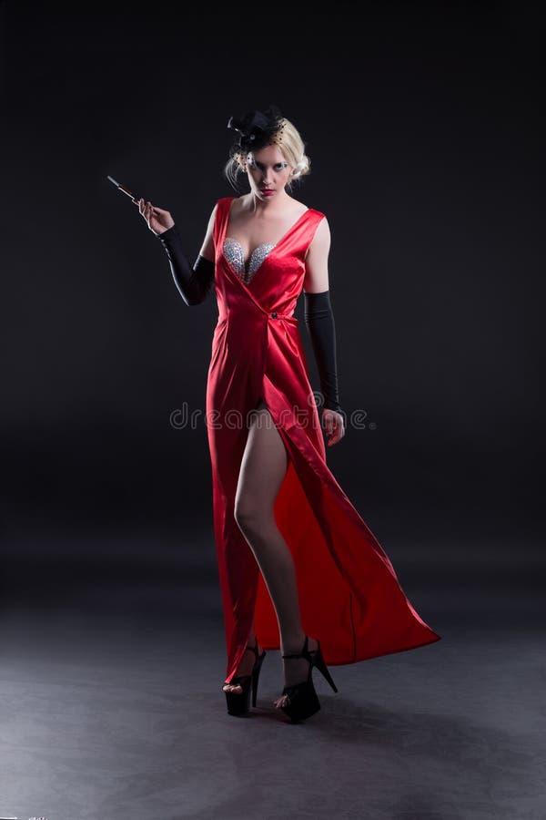 flicka i en röd klänning med en cigarett, i kabaret royaltyfria bilder