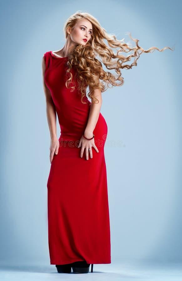 Flicka i en röd klänning med flyghår arkivbilder