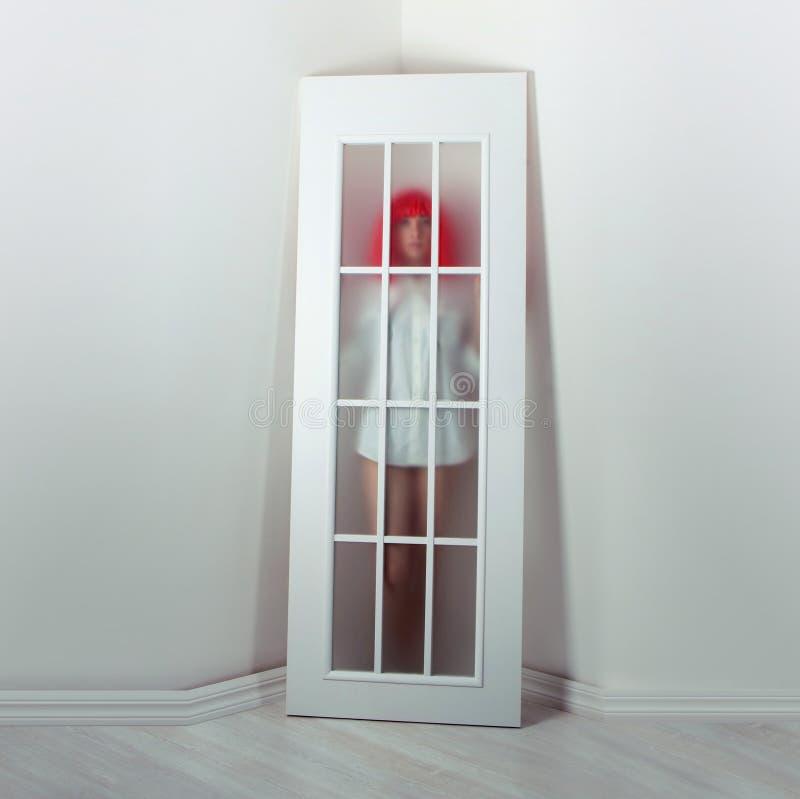 Flicka i en röd peruk och en vit dörr royaltyfria foton