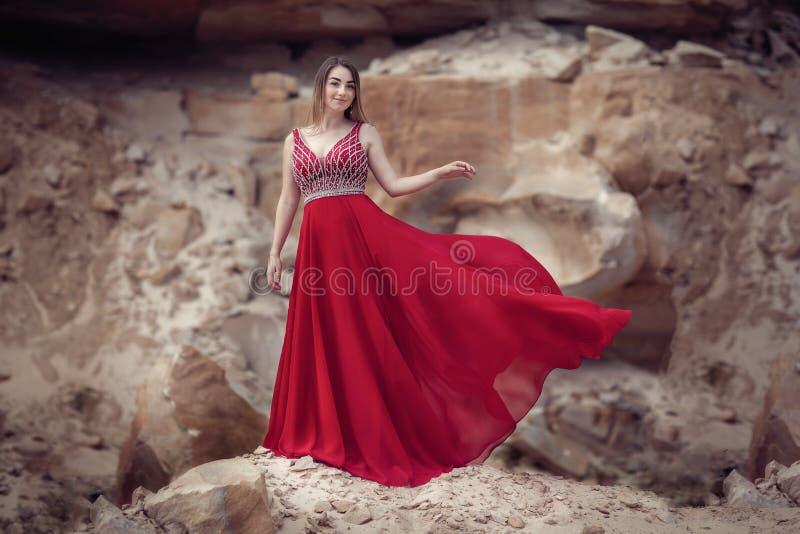Flicka i en röd vinkande klänning på en bakgrund av stenar royaltyfri bild