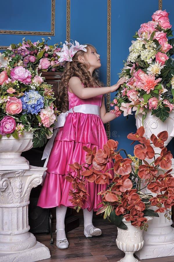 Flicka i en rosa klänning bland blommorna arkivbild