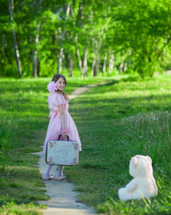 Flicka i en rosa klänning med en resväska som promenerar skogbanan arkivbilder
