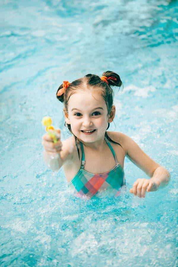 Flicka i en simbassäng med en vattenpistol royaltyfri bild